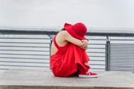 坐在木凳上抱腿的红衣女人图片素材