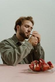 穿绿夹克的男人点燃香烟高清图片