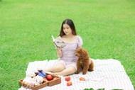 草地狗狗陪美女看书图片