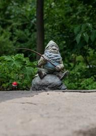 坐在岩石上的侏儒石雕高清图片
