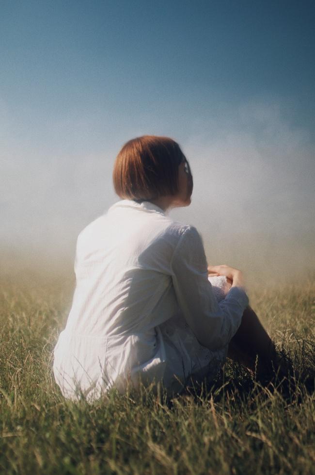 坐在杂草地上的美女背影图片
