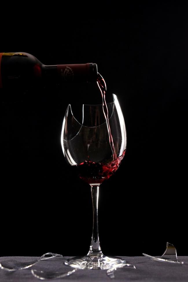 倒在破碎酒杯中的红酒高清图片