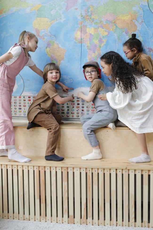孩子们指着墙壁学习世界地图图片